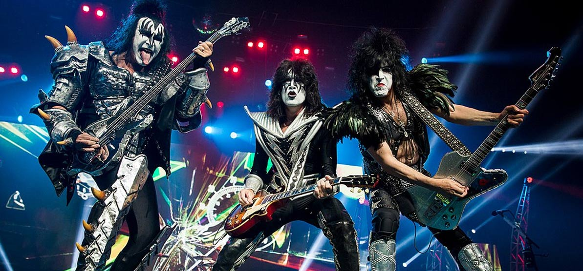 Kiss playing in 2013 during their Monster World Tour. From left to right: Gene Simmons, Eric Singer (in the background, on drums), Tommy Thayer and Paul Stanley.